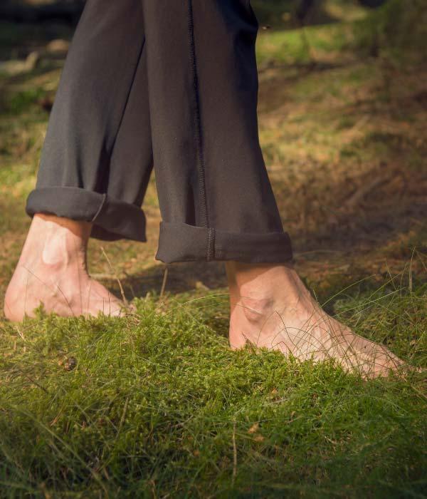 A man walking barefoot on grass