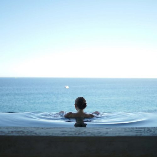 a woman In an overflow pool, overlooking the water