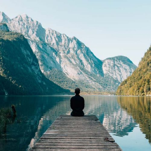 a person sitting looking at the lake and mountains