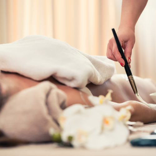 Young woman relaxing at luxury spa and beauty center during Asian treatment for skin rejuvenation